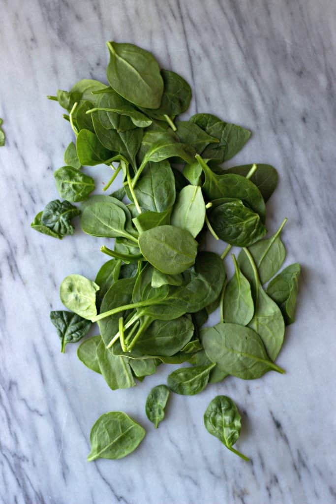 Overhead shot of fresh spinach spread on a marble surface
