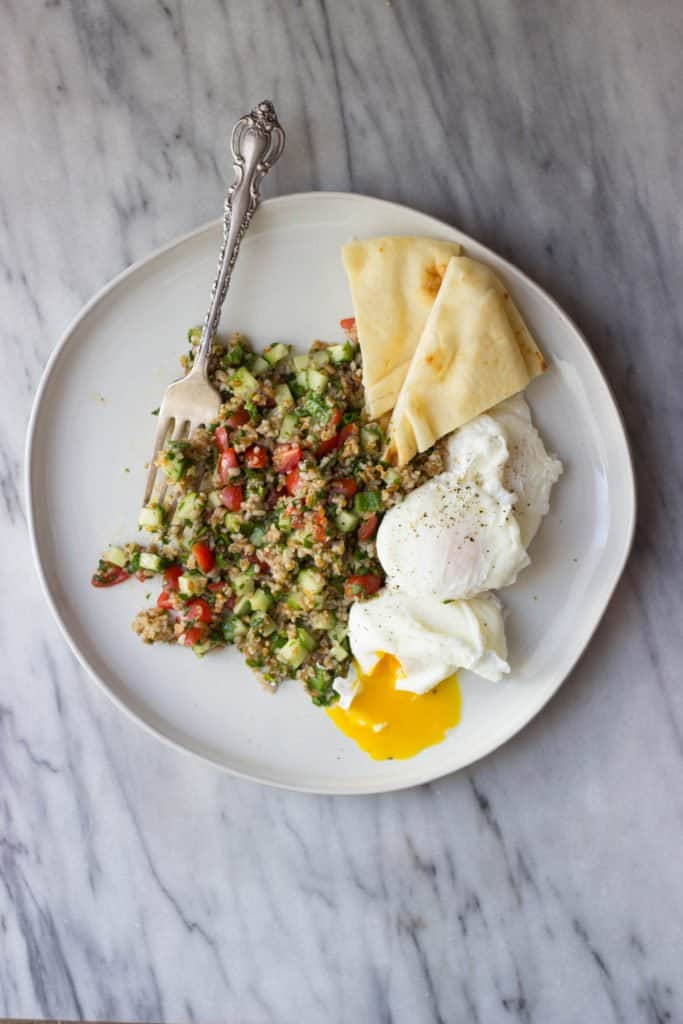 Overhead view of breakfast tabbouleh with poached eggs and pita wedges and egg yolk seeping out of one egg