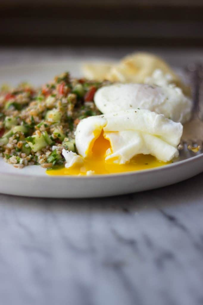 Side shot of breakfast tabbouleh on a plate with egg yolk coming out of a poached egg