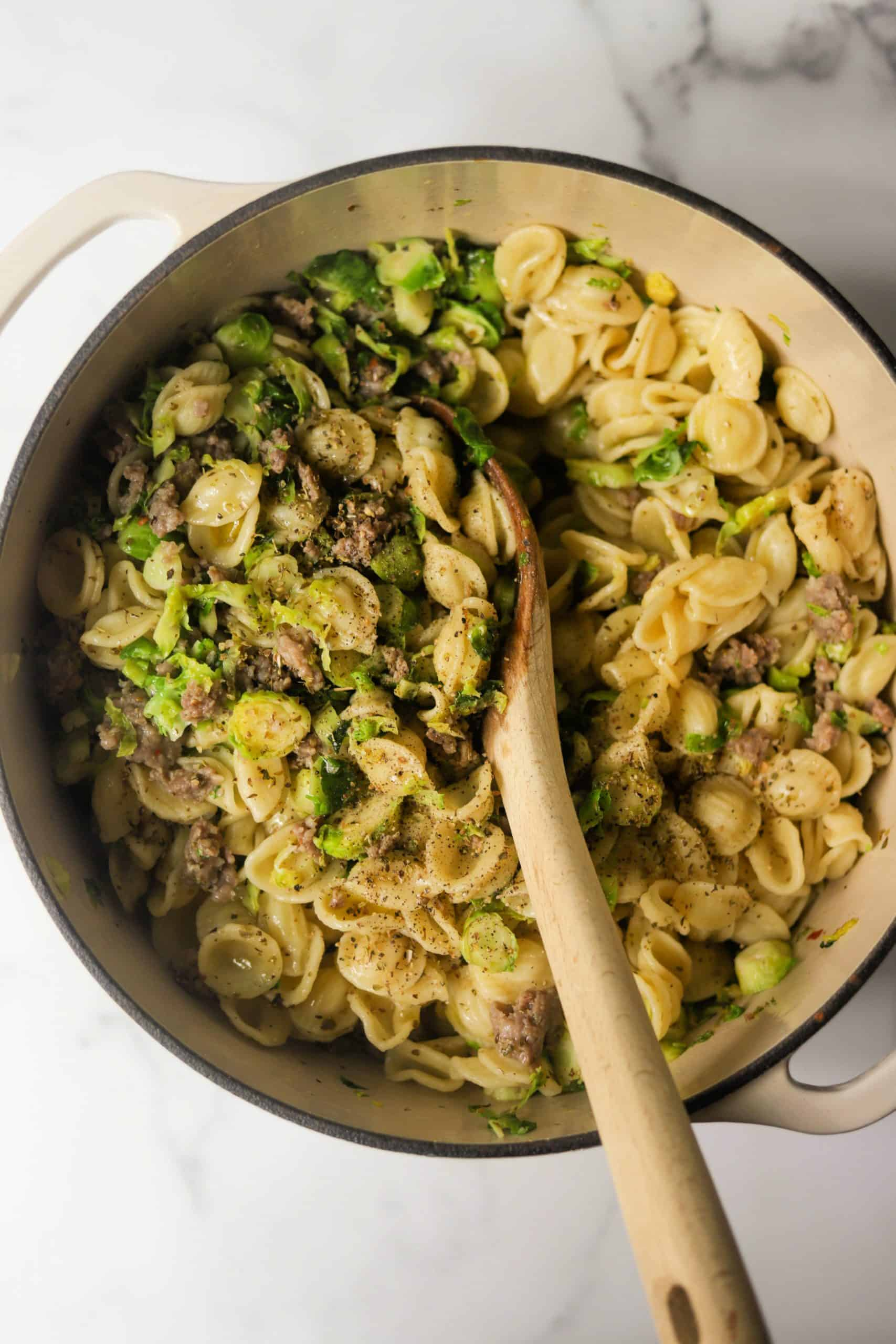 A white pot filled with sausage pasta.