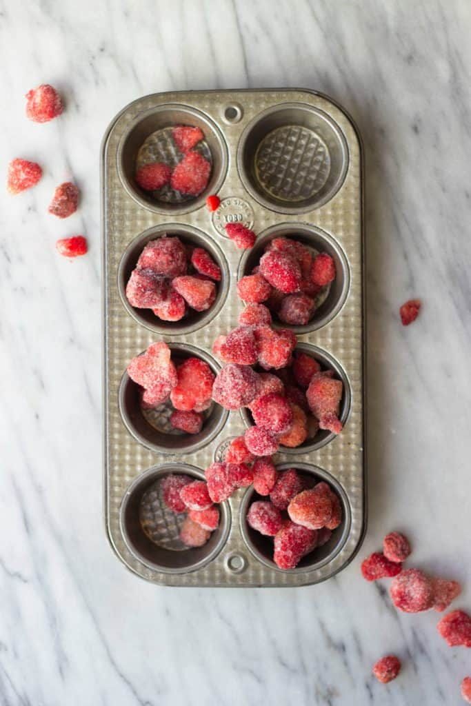 Overhead shot of frozen Strawberries on top of a tin pan.
