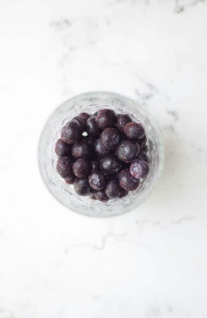 Overhead shot of blueberries in a glass bowl.