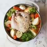 Chicken stock ingredients in a white Dutch oven
