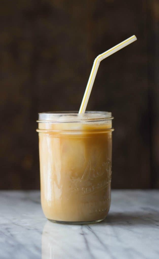 Stirred Coconut Caramel Cold Brew Coffee with a straw in a mason jar.