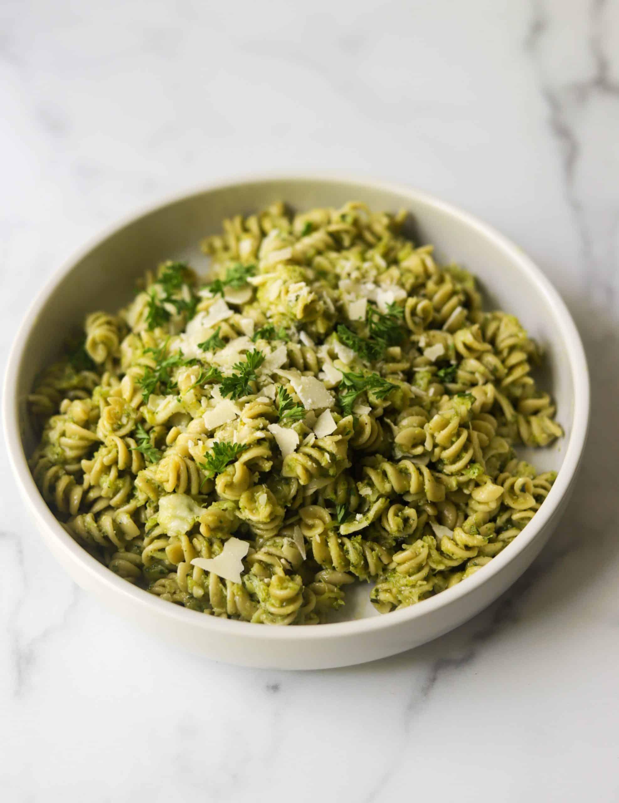 A white bowl filled with broccoli pesto pasta.