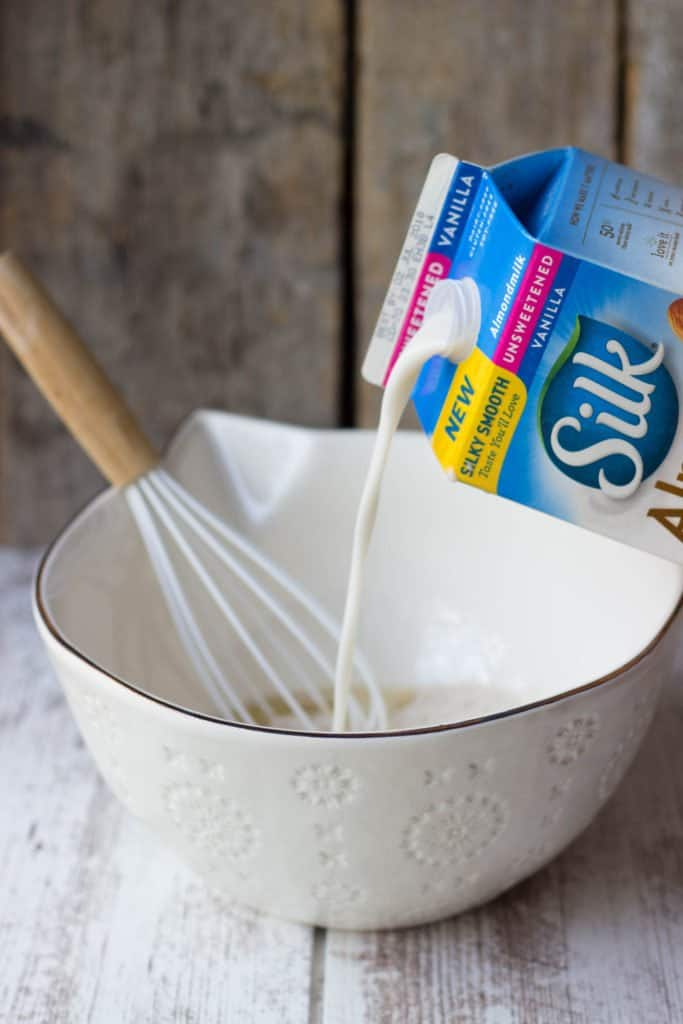 Side view of Silk Almondmilk pouring into a mixing bowl.