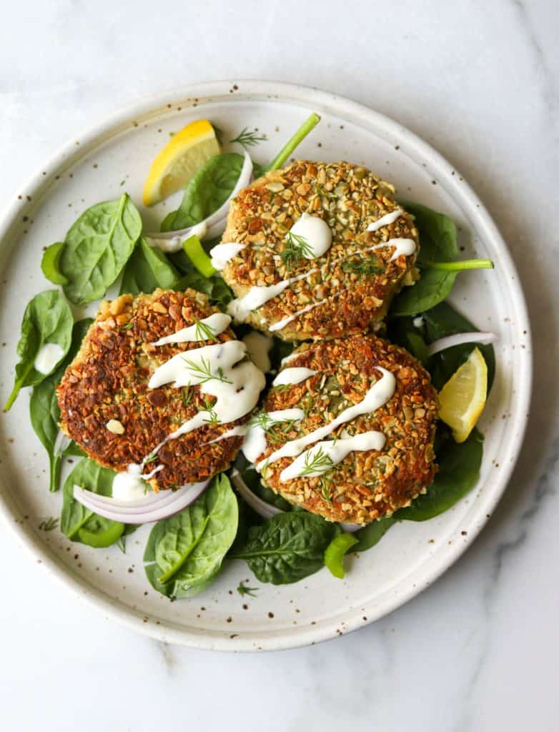 Crispy pepita-crusted tuna cakes on a bed of greens as an easy way to eat more fish.