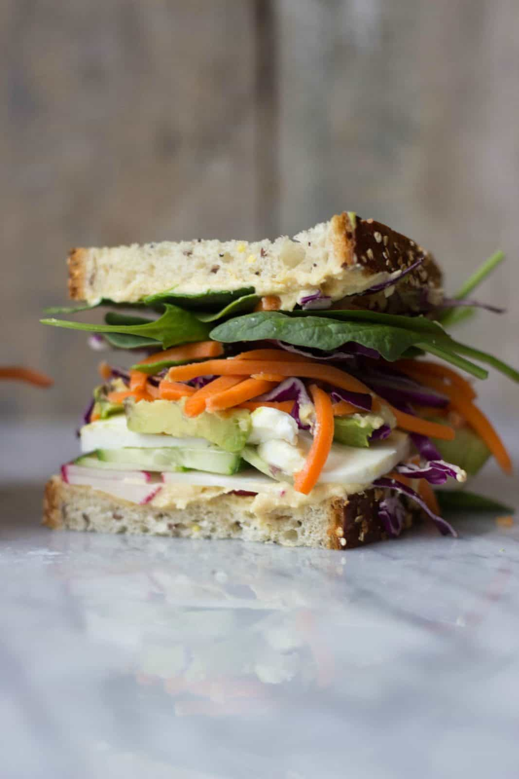 Side shot of a veggie sandwich on a white marble counter
