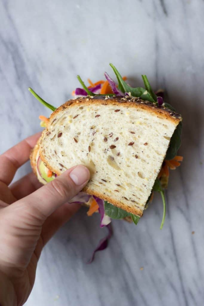 Overhead shot of a hand holding the  Ultimate Veggie Sandwich