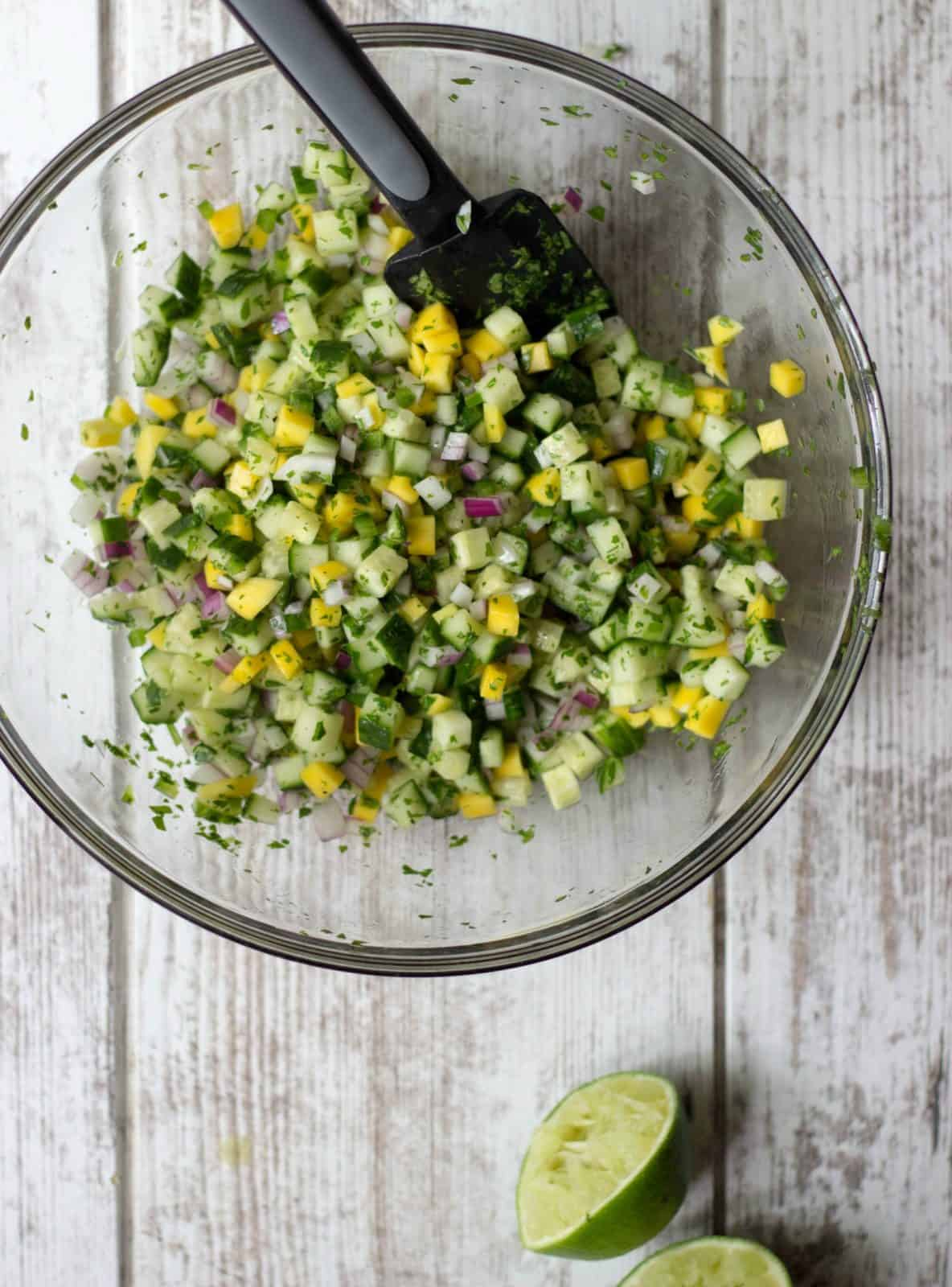 Mixed ingredients of Mango Cucumber Salsa in a glass bowl.