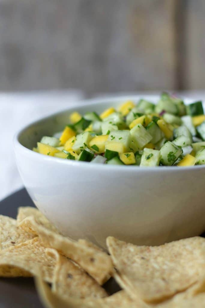 Side shot of Mango Cucumber Salsa in a white bowl next to tortilla chips.