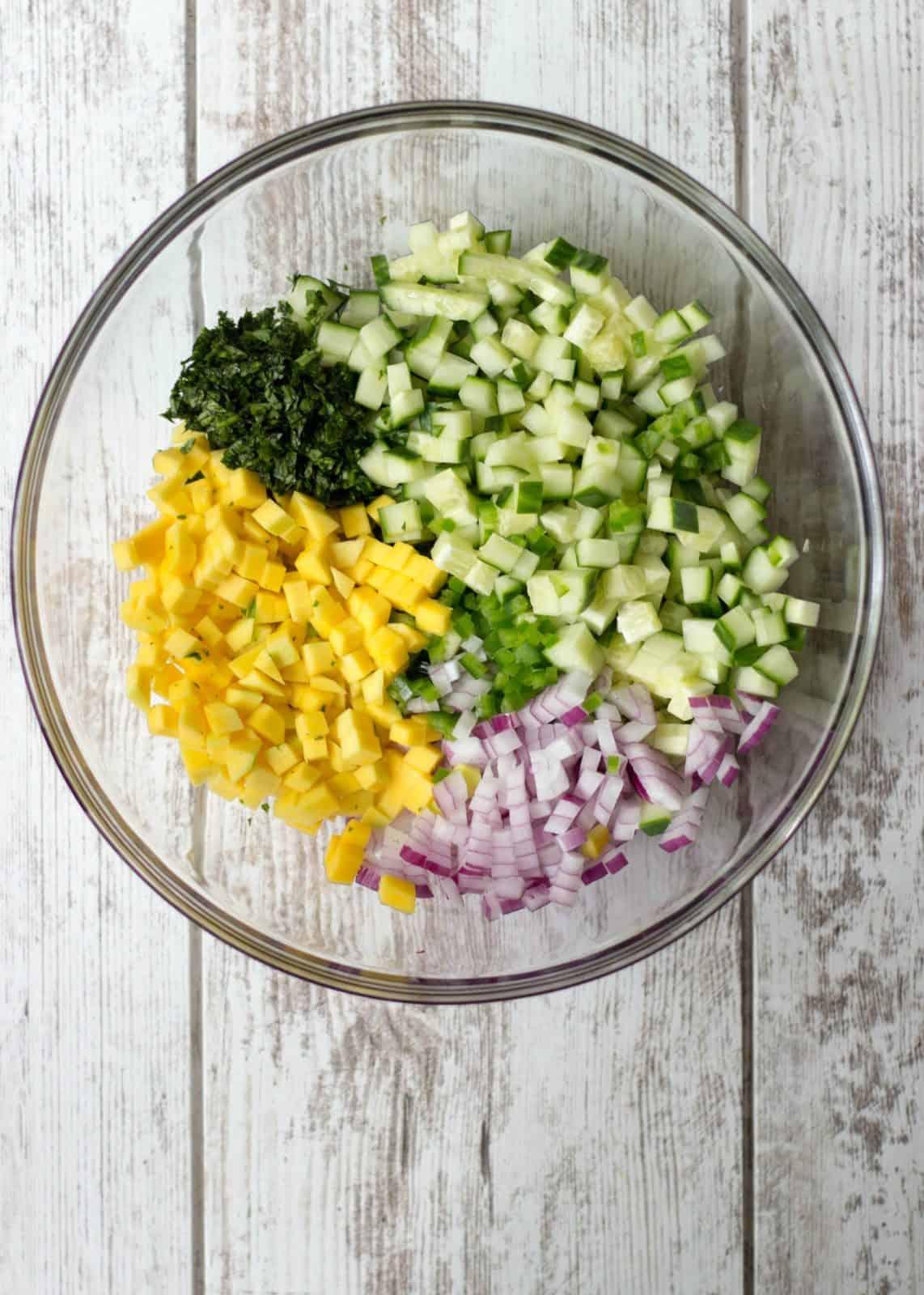Mango Cucumber Salsa ingredients separate in one bowl.