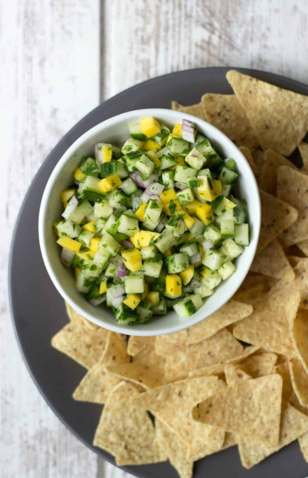 Overhead shot of Mango Cucumber Salsa in a white bowl with tortilla chips next to it.