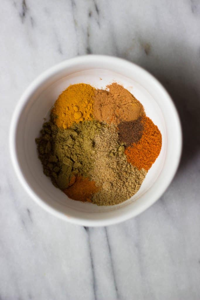 Overhead shot of spices in a white bowl.
