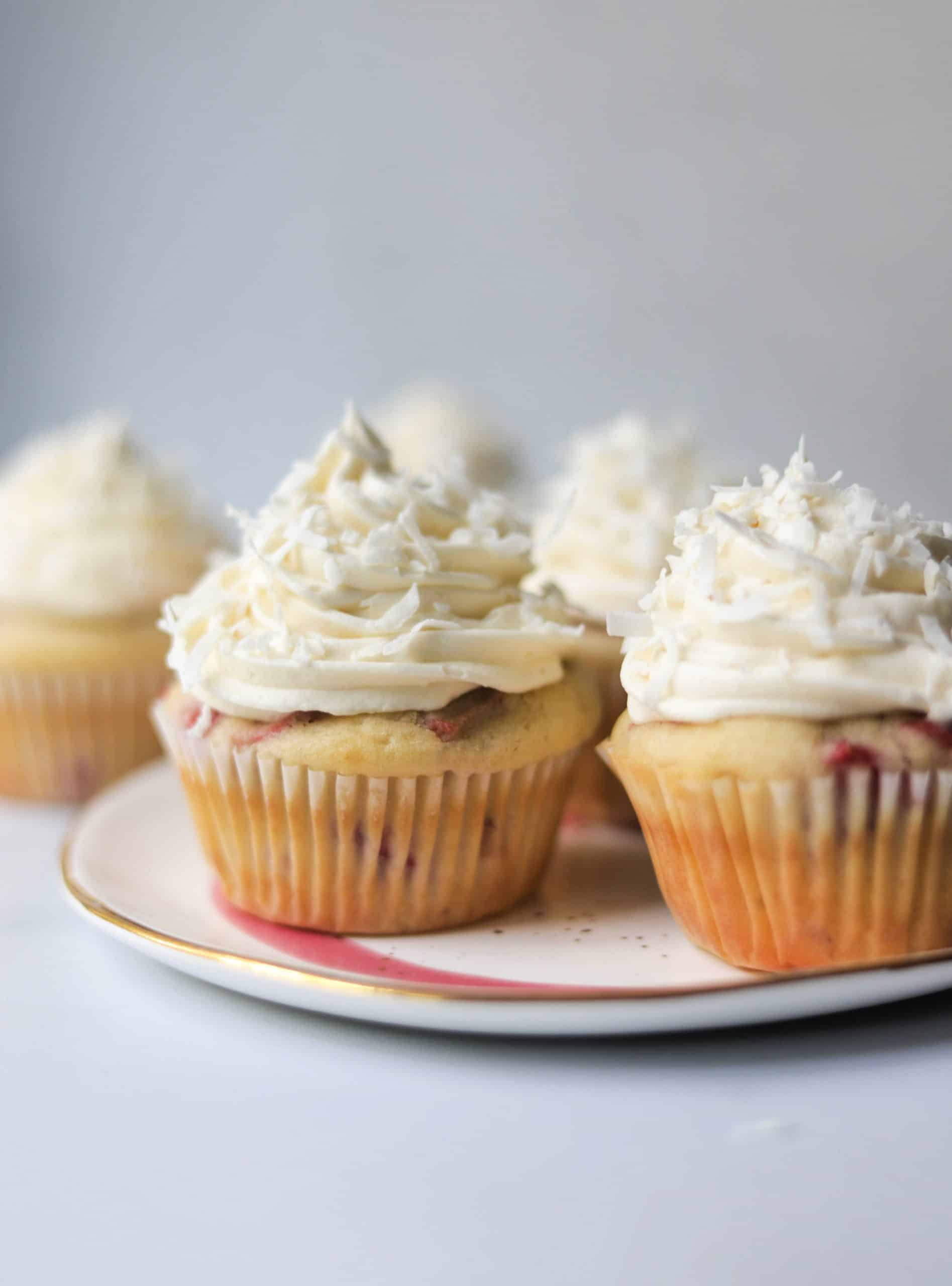 A plate filled with strawberry rhubarb cupcakes on a marble backdrop.