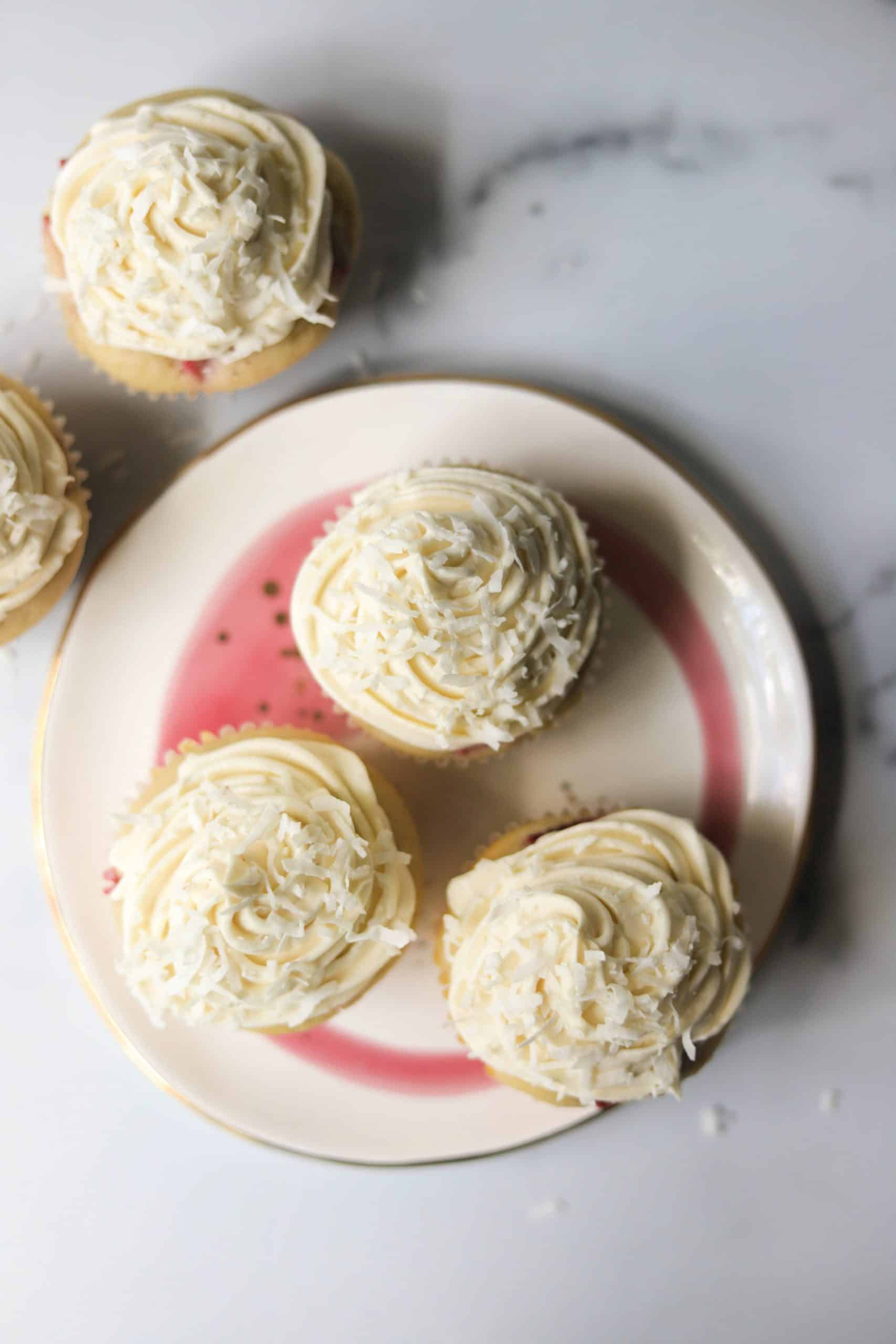 A birds eye view of a plate with 3 strawberry rhubarb cupcakes with 2 additional cupcakes on the side on a marble board.