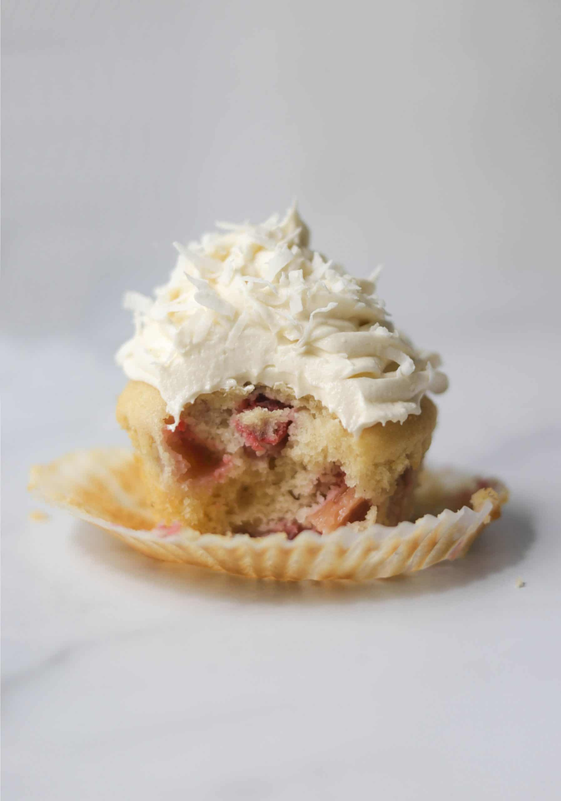 A marble board with one strawberry rhubarb cupcake with a bite out of it.