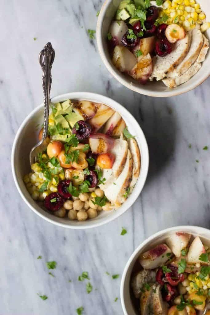 Grilled Peach & Sweet Corn Summer Grain Bowls in white bowls.