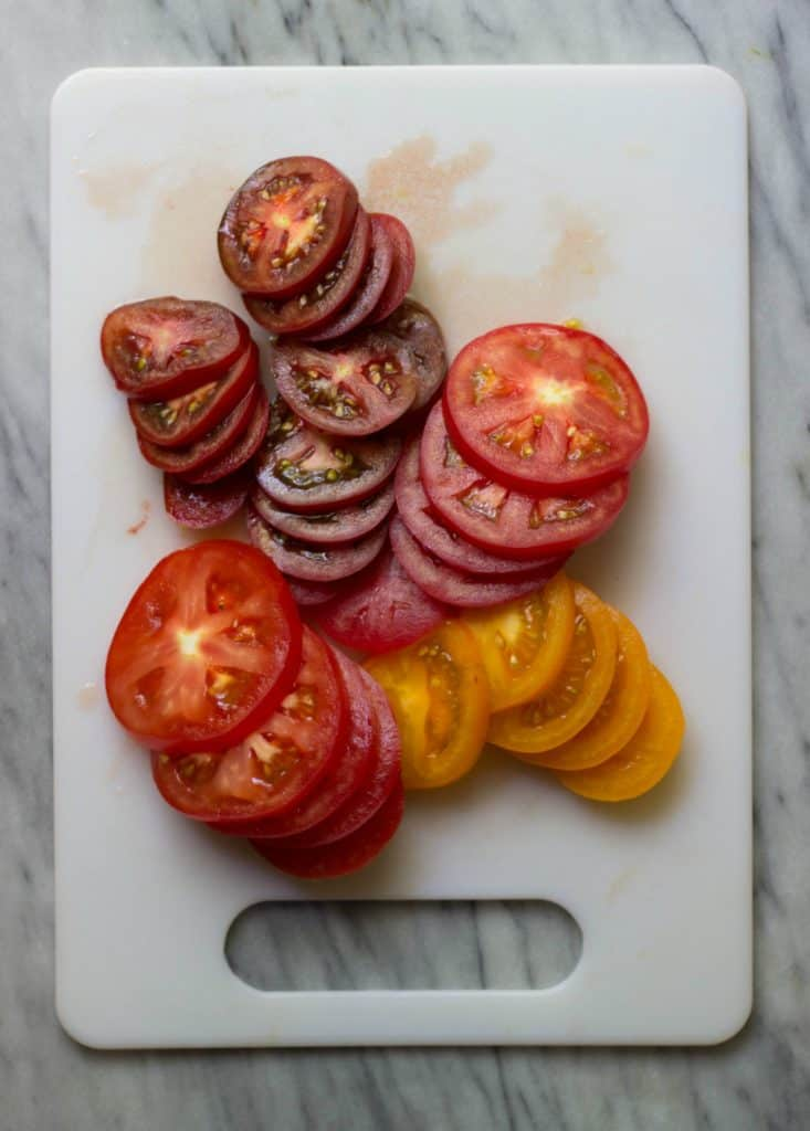 Heirloom Tomatoes on a white cutting board.