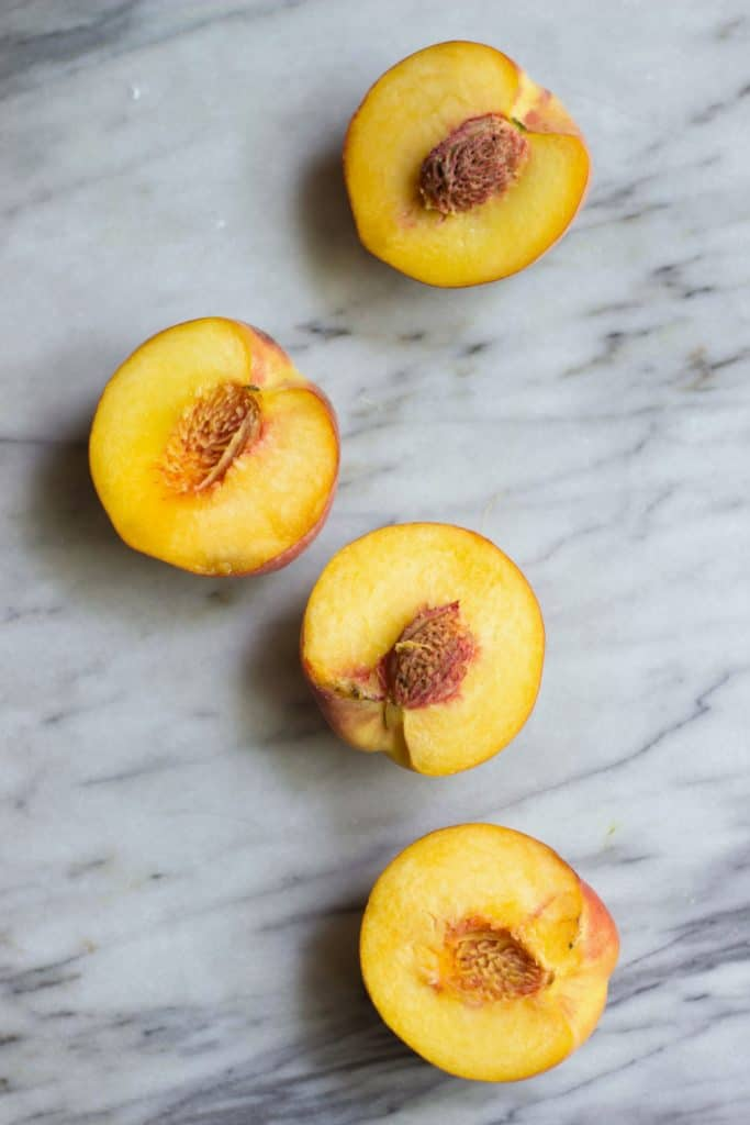 Grilled peaches on marble board.