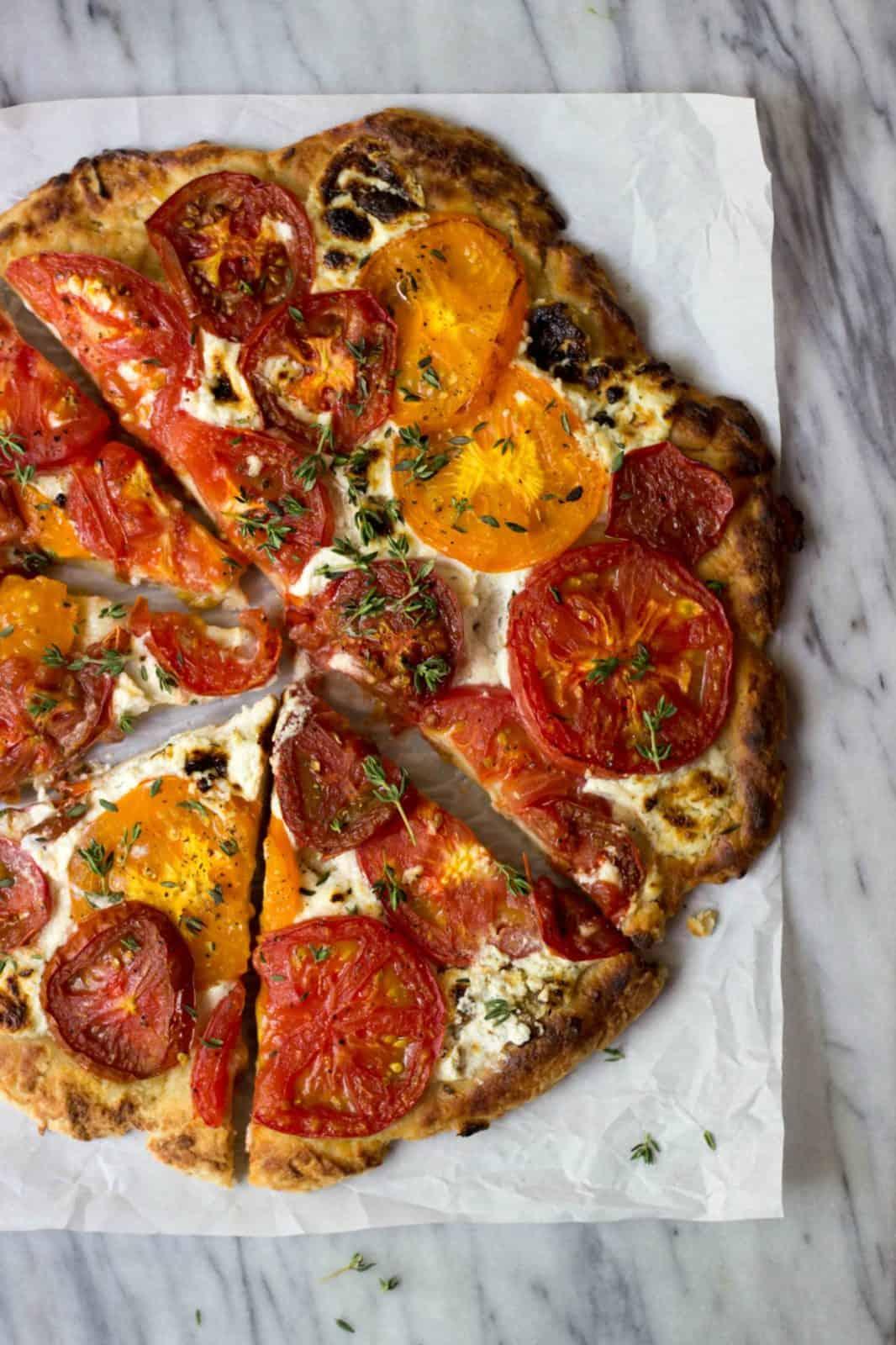 Vegetarian Rustic Heirloom Tomato Pizza on marble board.