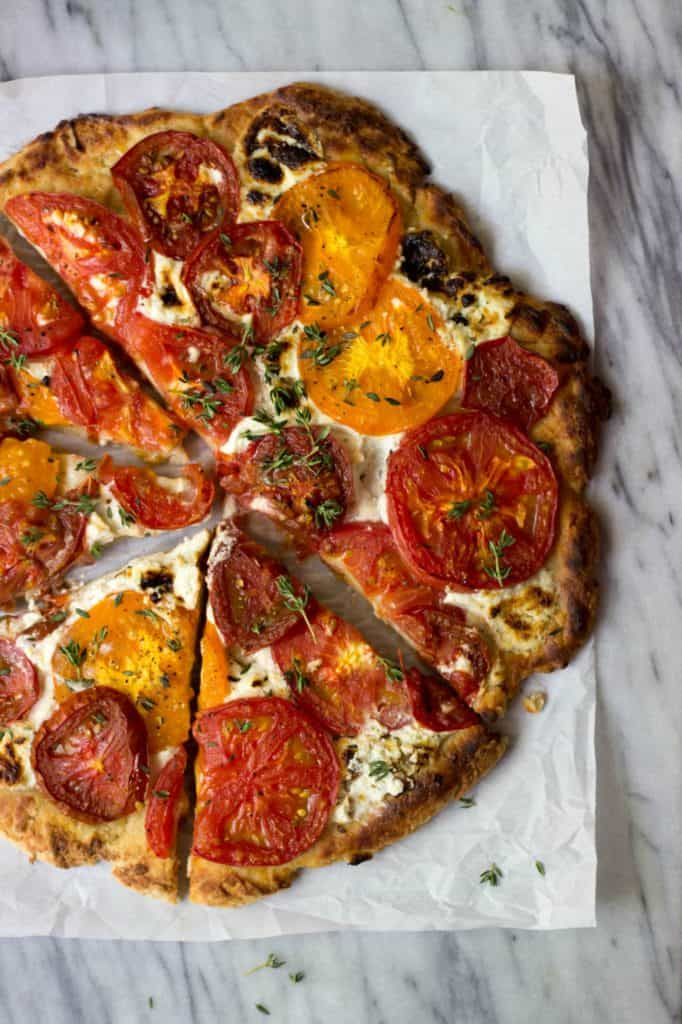 Rustic Heirloom Tomato Pizza on a marble board.