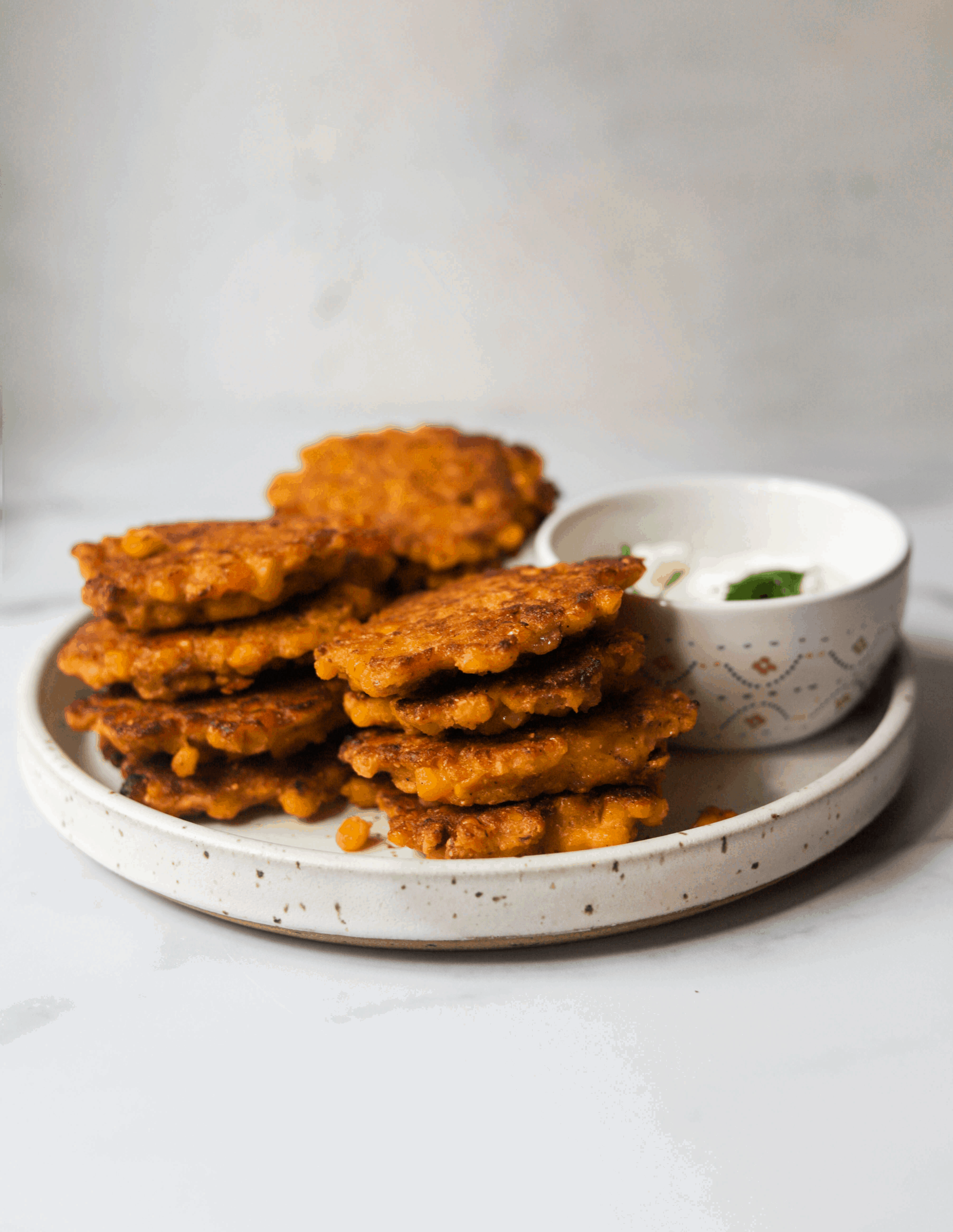 A white speckled plate with corn fritters stacked and a small bowl with dipping sauce.