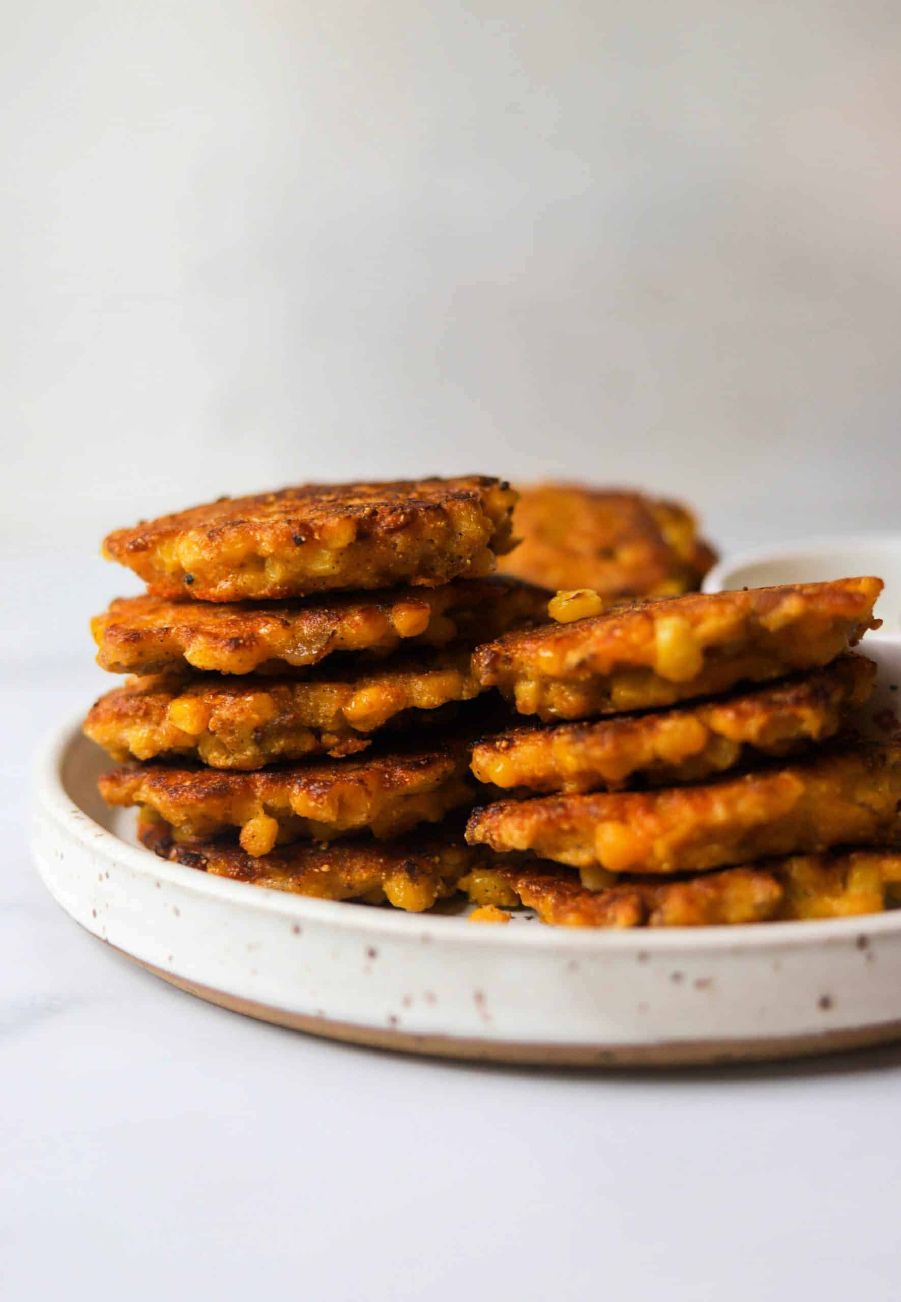 A white speckled plate with stacks of bacon and corn fritters.