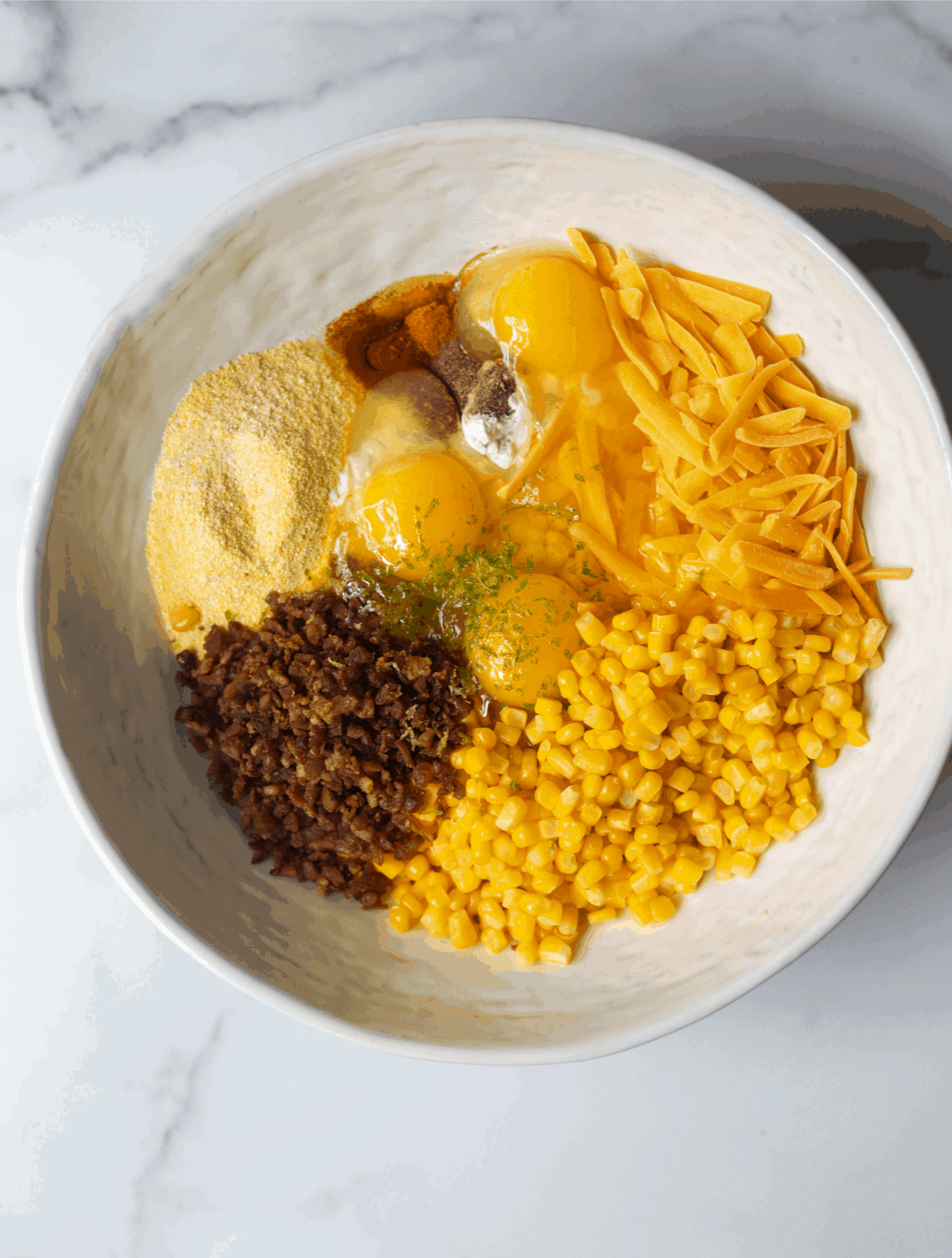 A white bowl with bacon and corn fritter ingredients.