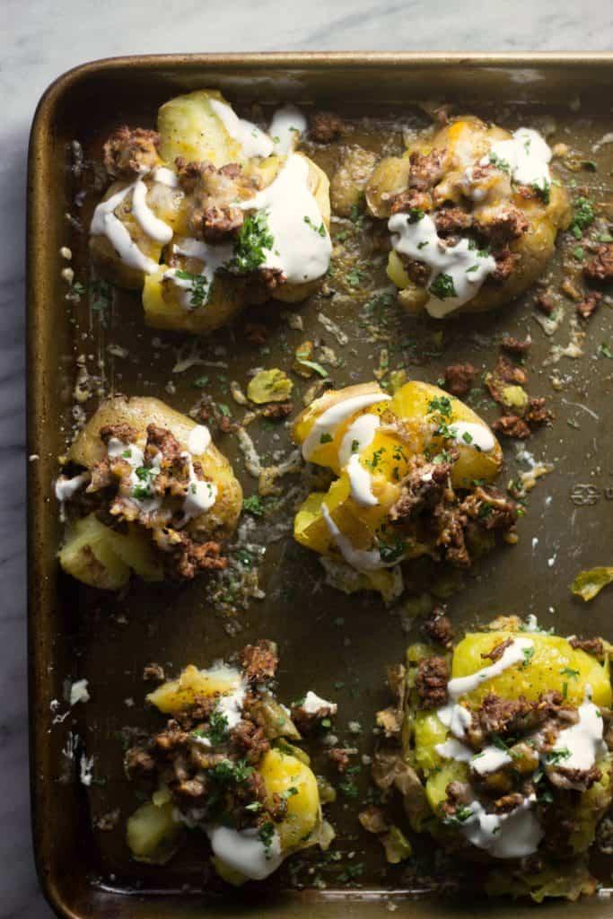 Taco-Stuffed Smashed Potatoes on a baking sheet.