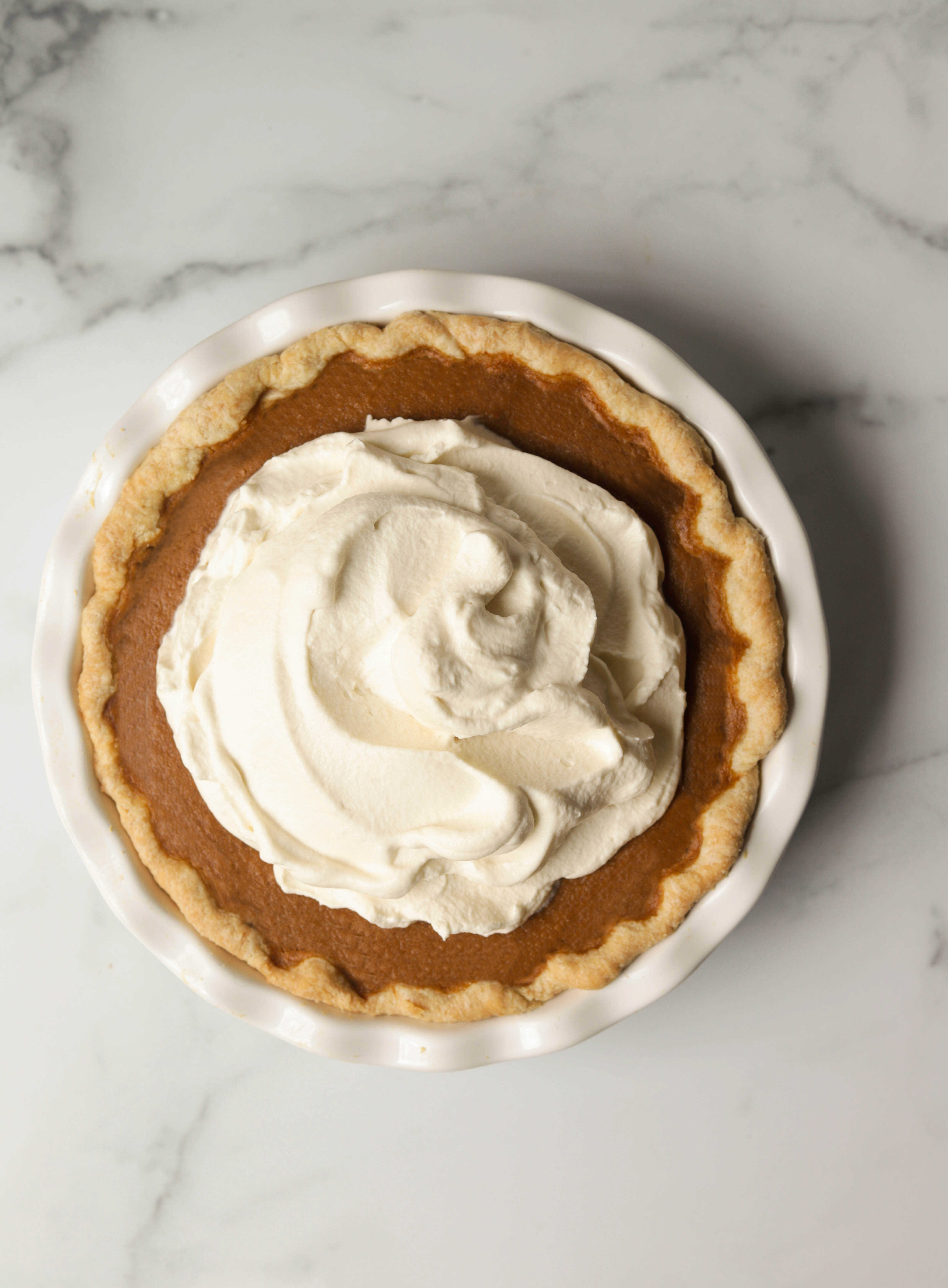 An overhead shot of a sweet potato pie with whipped cream on top.
