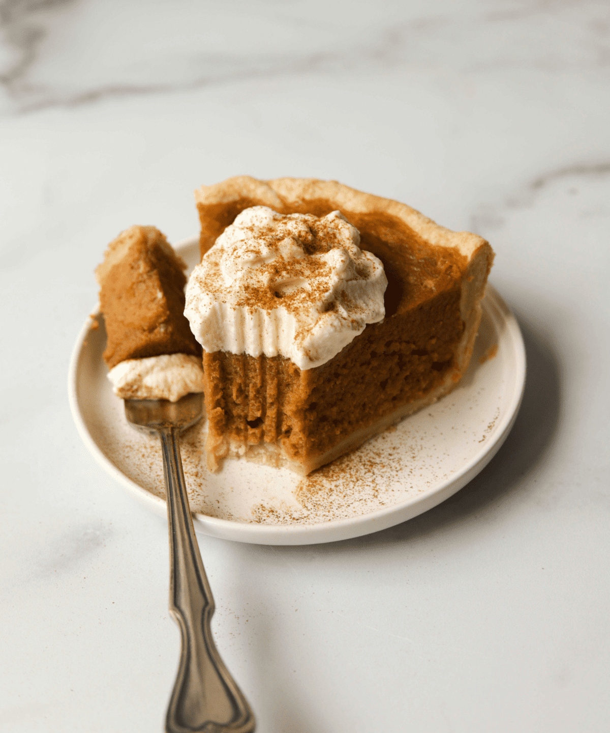 A slice of sweet potato pie with whipped cream on top with a bite missing and a fork on the side.