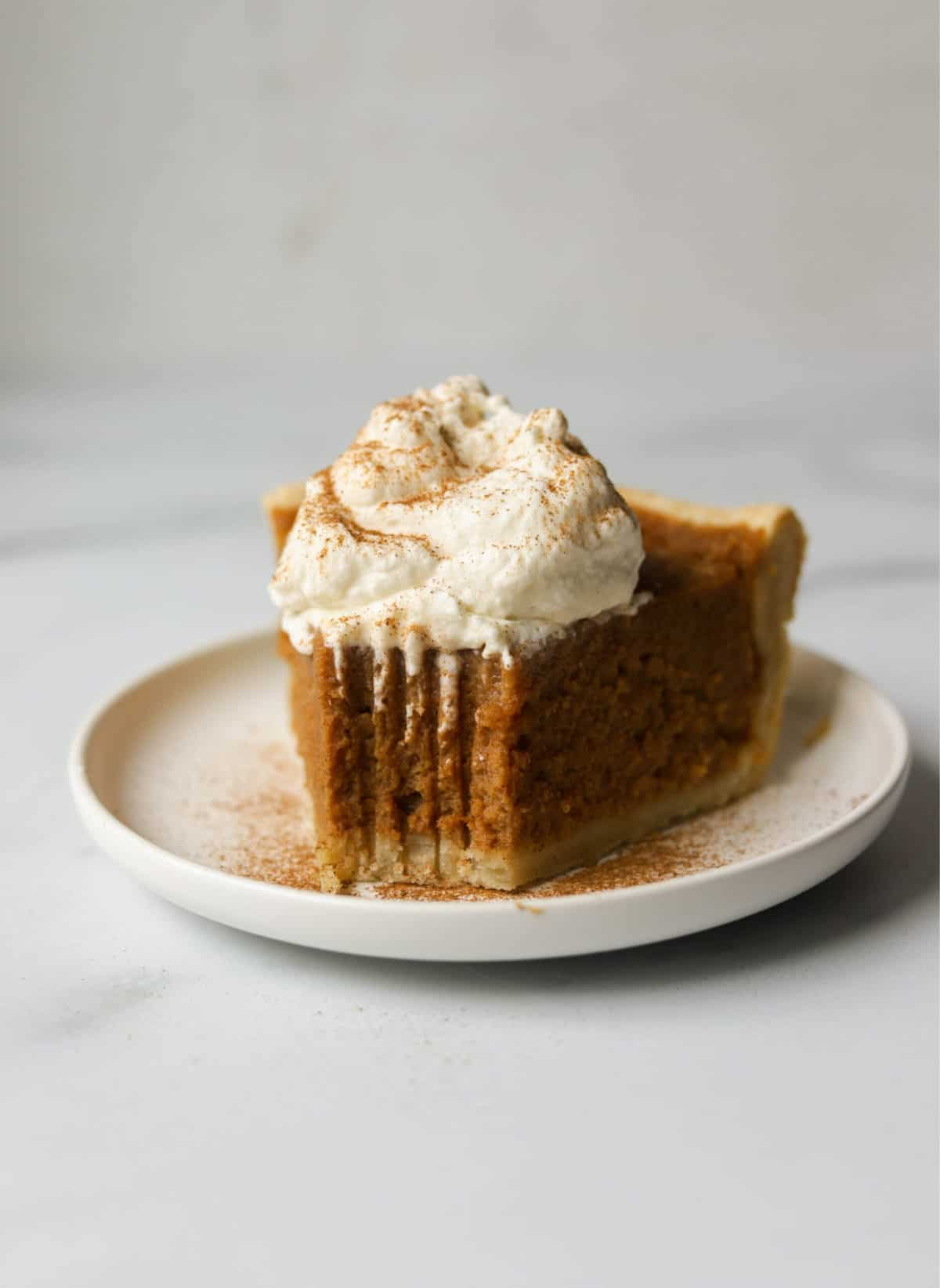 A side shot of a slice of sweet potato pie with a bite taken out of it.