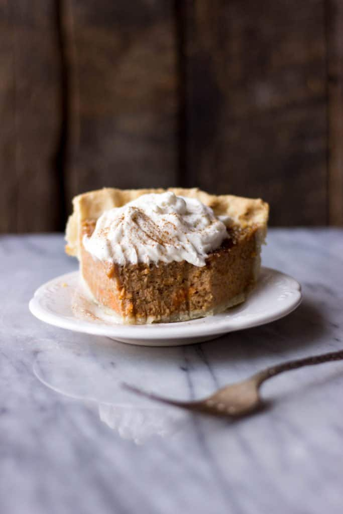 Sweet Potato Pie with Maple Whipped Cream on white plate.