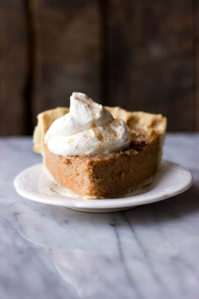 Sweet Potato Pie with Maple Whipped Cream on a white plate.