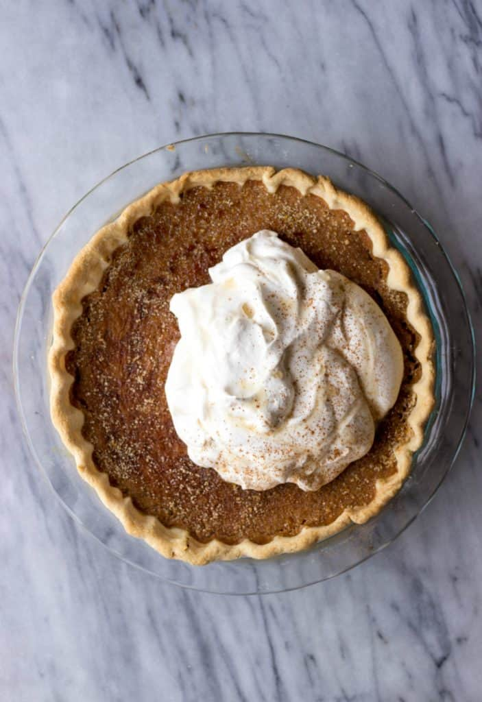 Sweet Potato Pie with Maple Whipped Cream in pie plate.