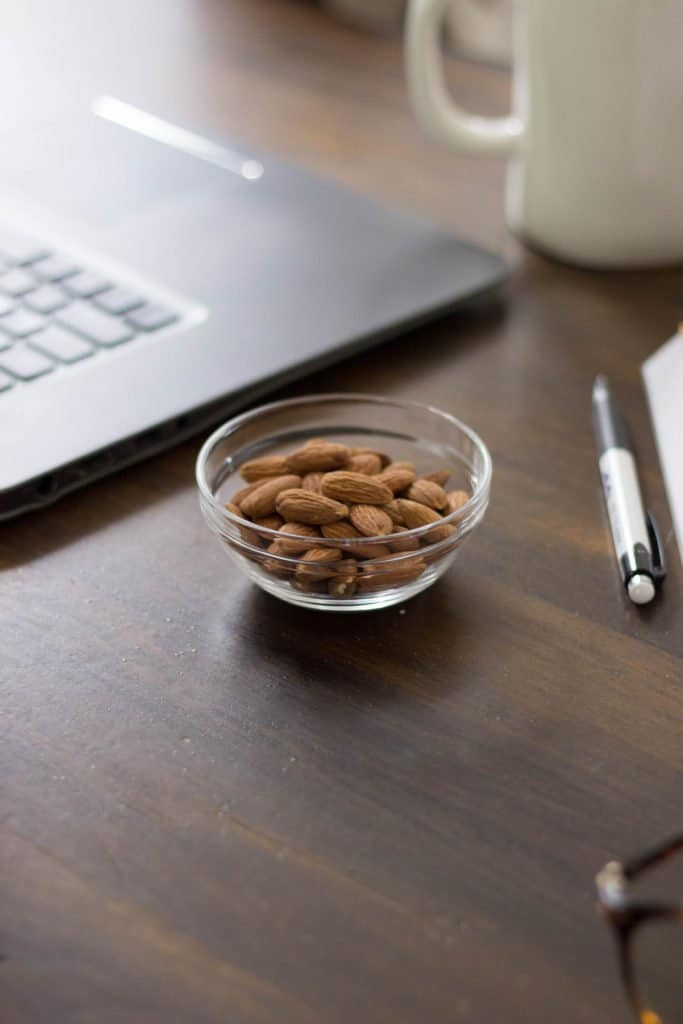 Almonds in a bowl next to a computer on a desk.