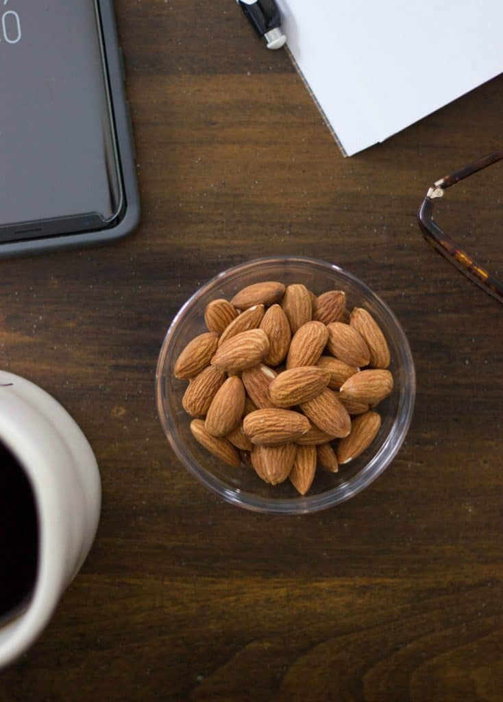 Overhead shot of almonds in a glass bowl.