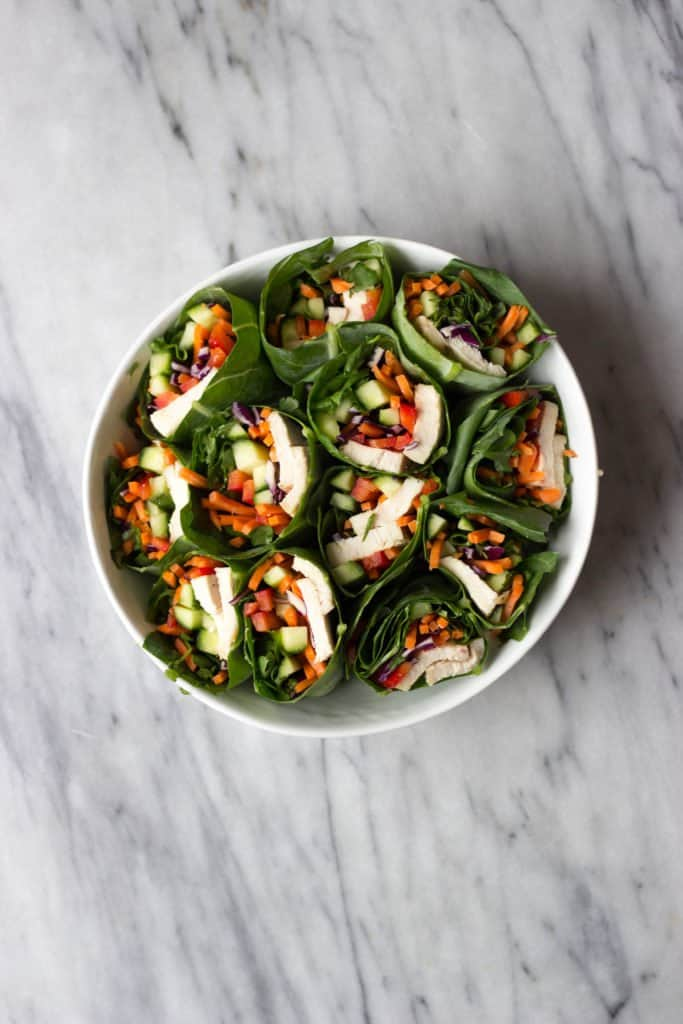 Hummus & Vegetable-Stuffed Collard Wraps on white plate.