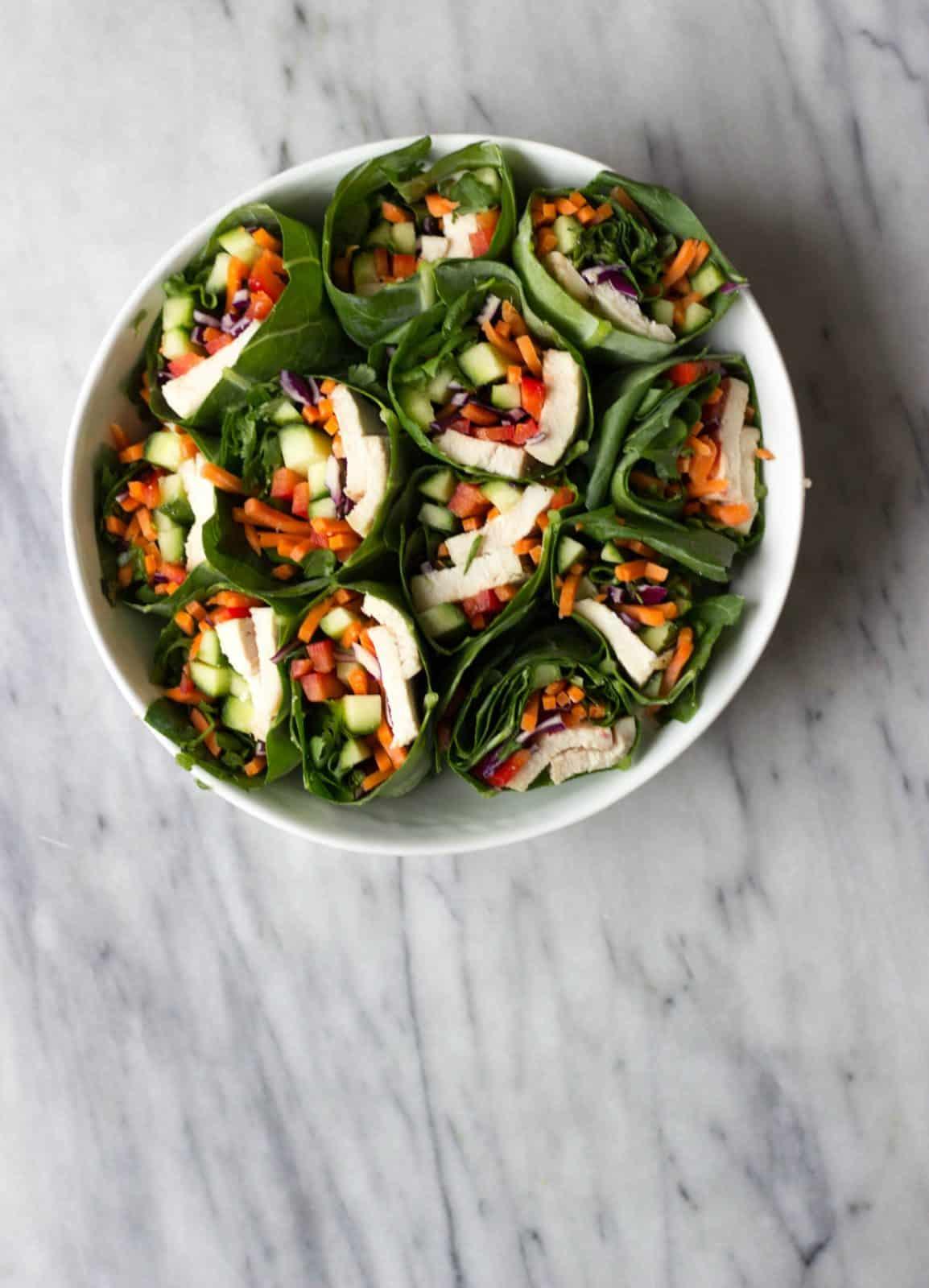 Hummus & Vegetable-Stuffed Collard Wraps in white bowl.
