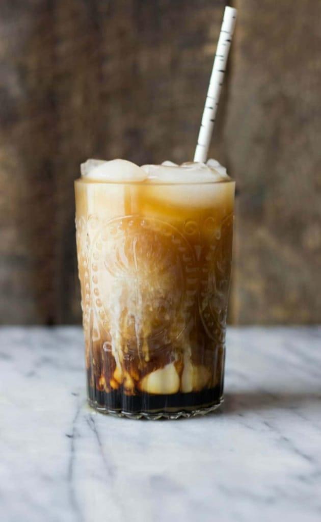 Cold Brew Coconut Vanilla Macchiato with a straw on a marble table