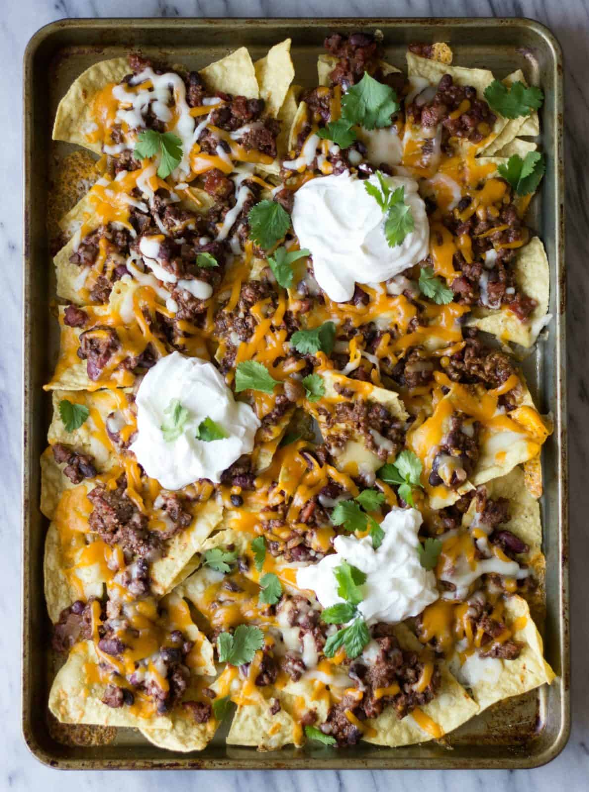 Chili Nachos on a sheet pan made with black and dark red kidney beans.