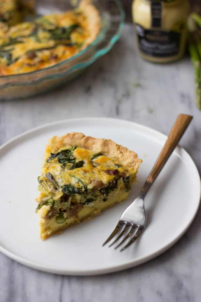 One slice of Asparagus & Sausage Quiche on a white plate