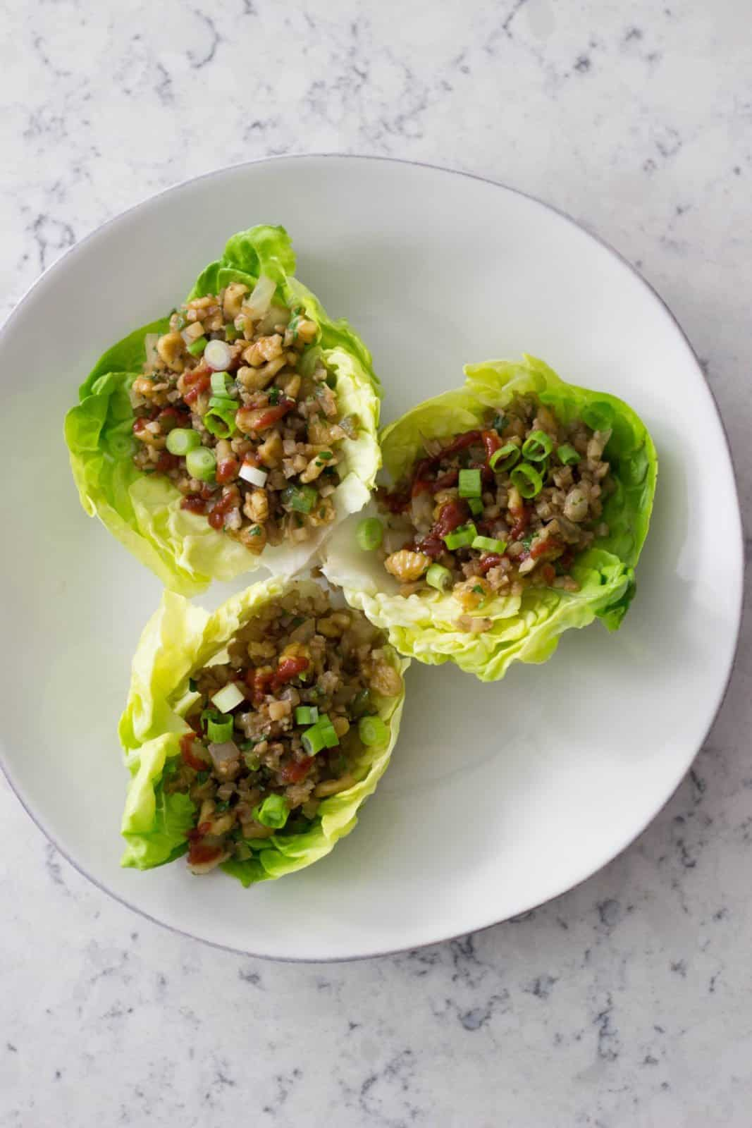 Overhead shot of three Thai-Style Cauliflower Walnut Lettuce Cups on a white plate