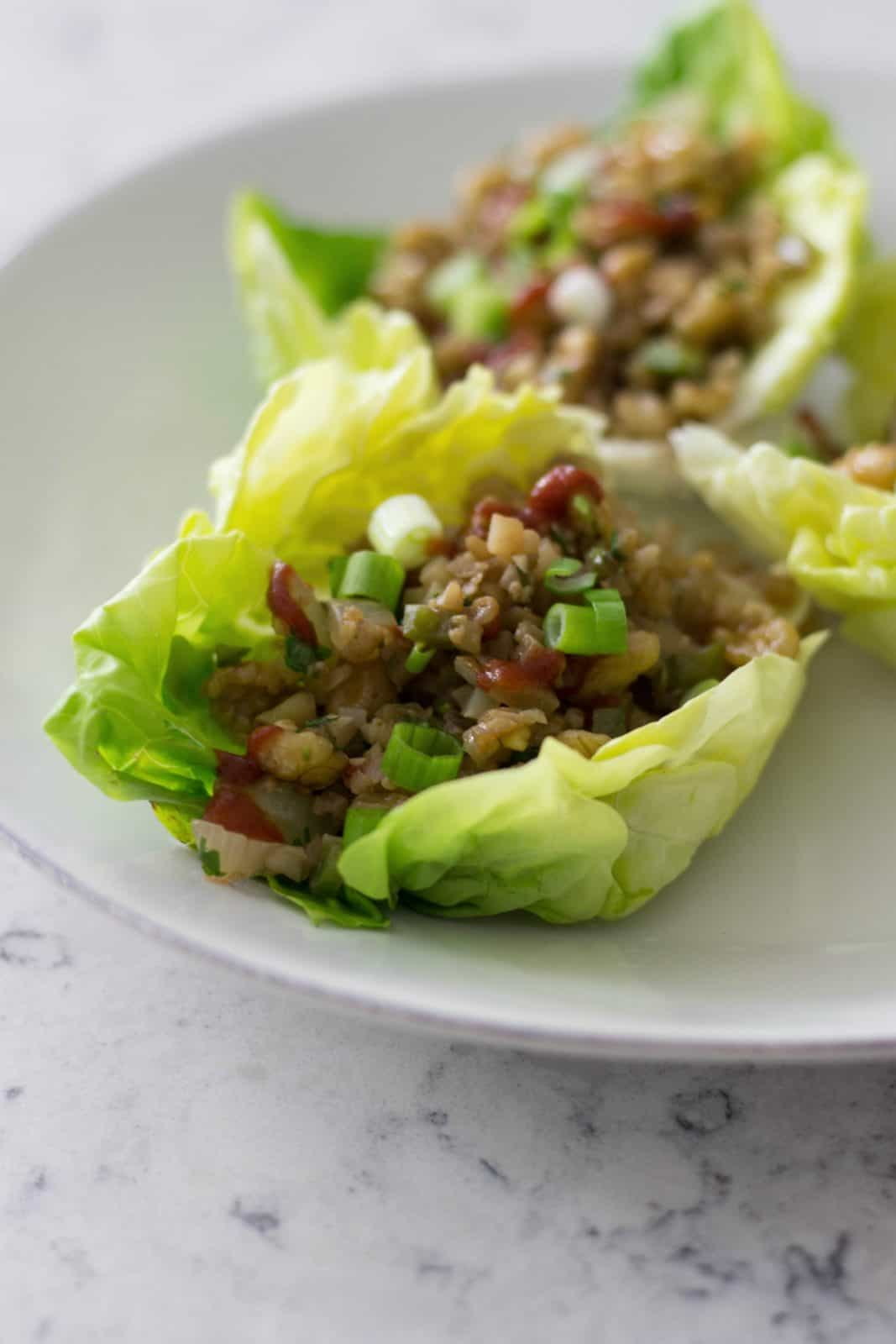 Side close-up shot of lettuce cups on a white plate