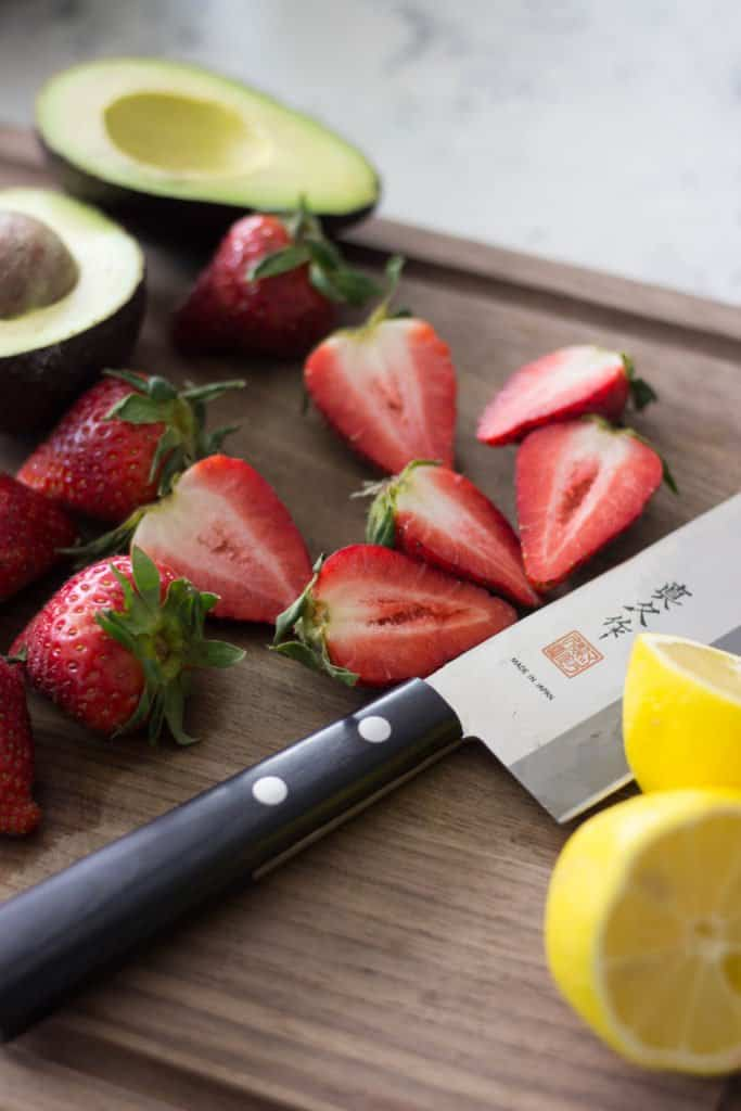 Fresh strawberries laying next to a lemon and a knife on a cutting board