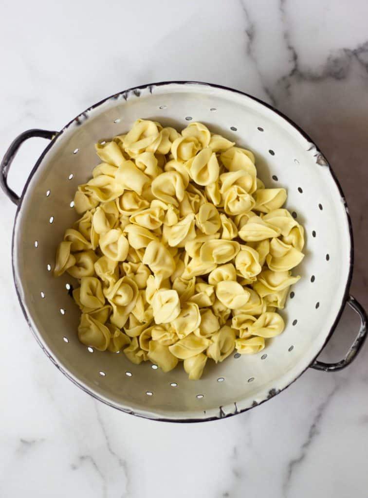 Tortellini in a white colander