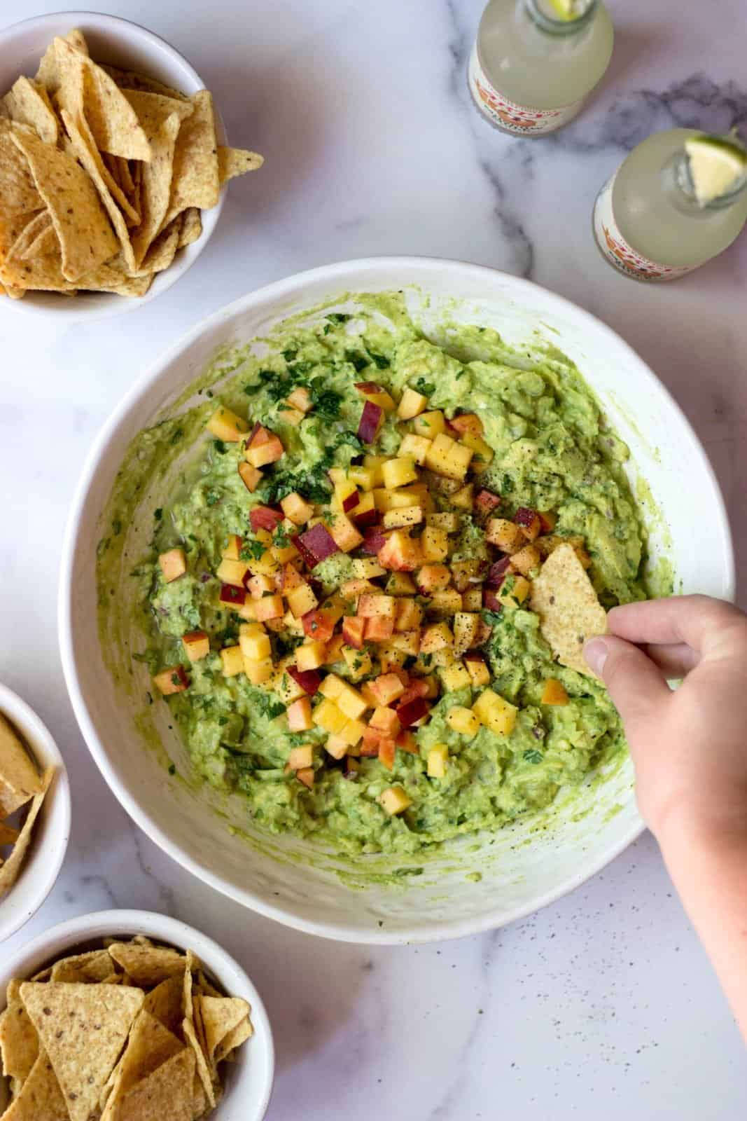 Peach guacamole in a white bowl with a hand and chip dipping into it