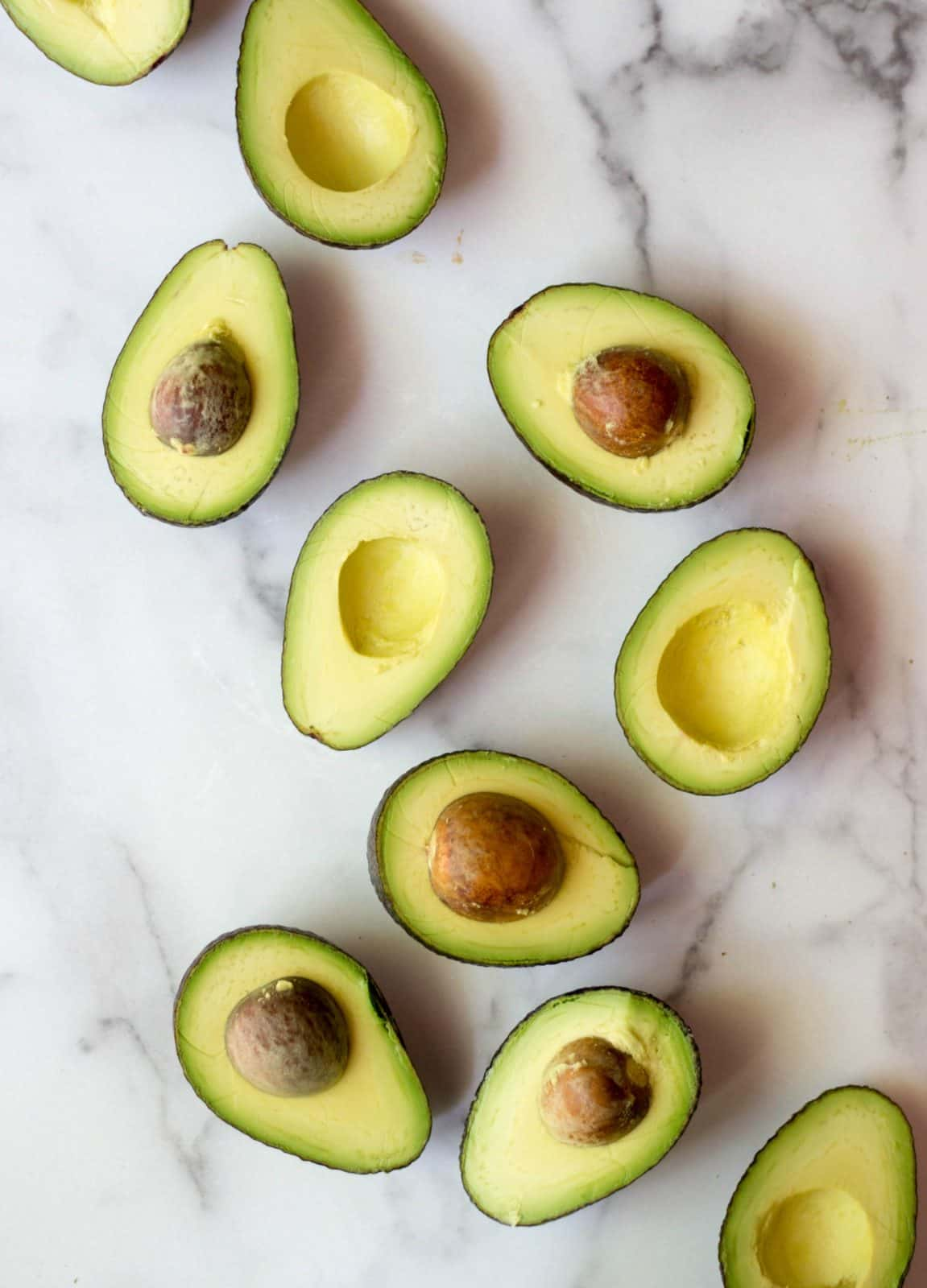 Halved avocados on a white marble background