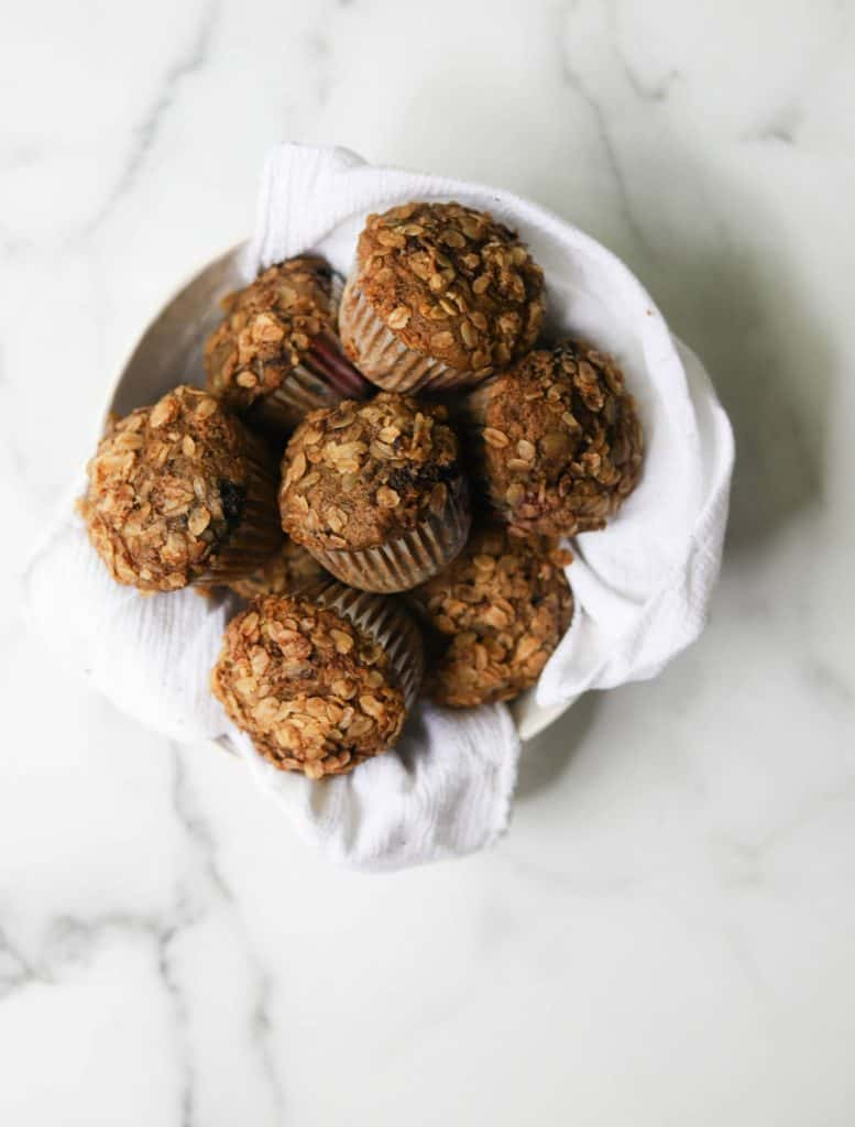 Overhead shot of Mixed Berry Crumble Muffins piled atop one another in a bowl